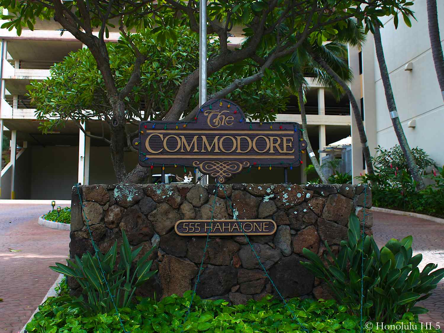 The Commodore Condo in Hawaii Kai Brown Entrance Sign With Bushes Around