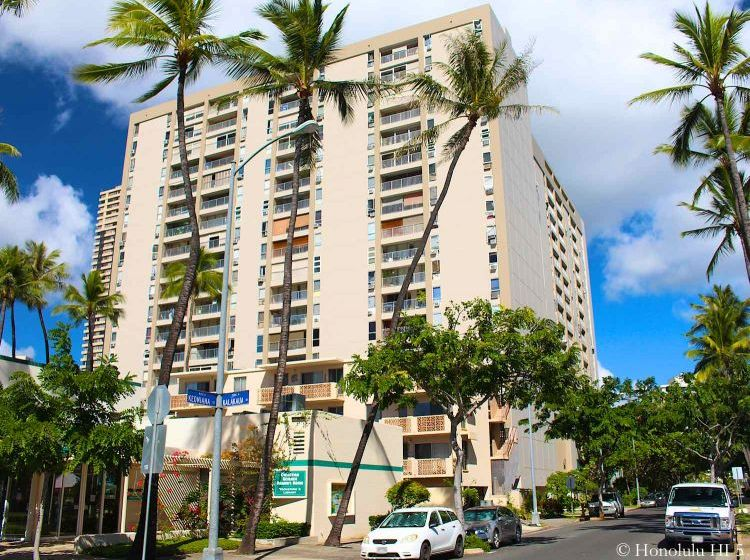Keoni Ana Condos in Waikiki - Yellowish Old High-Rise with Blue Sky and Palm Trees Around
