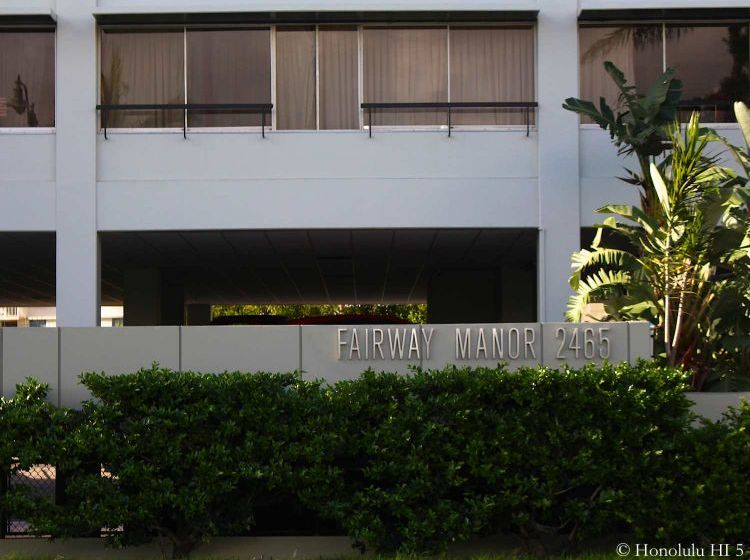 Lower Floor Of Fairway Manor Condo in Waikiki. Simple White Building with Some Bushes and Green in Front
