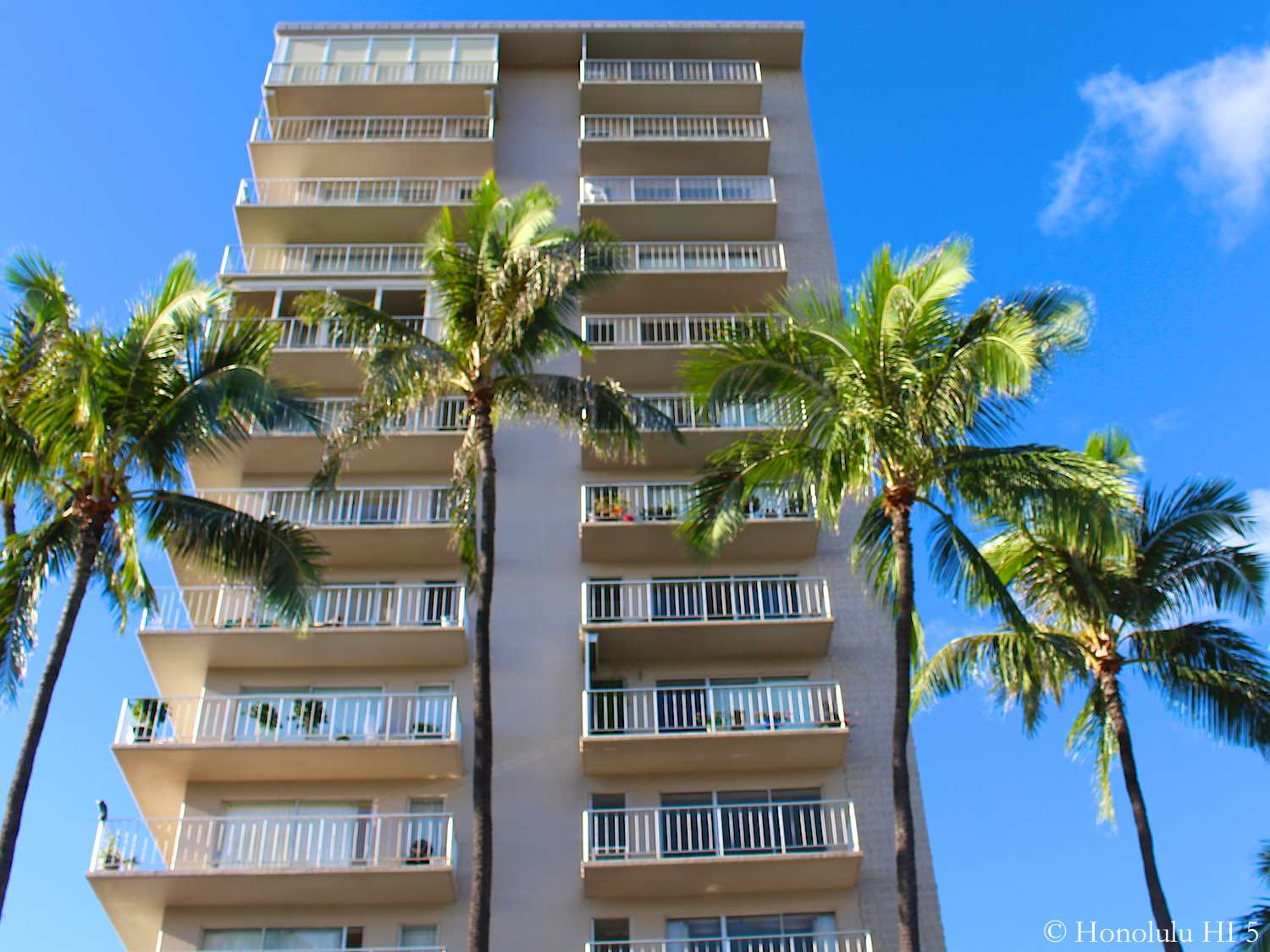 Hale Moani Condos in Waikiki. Narrow Old High-Rise Building in White with Lanais and Palm Trees in Front