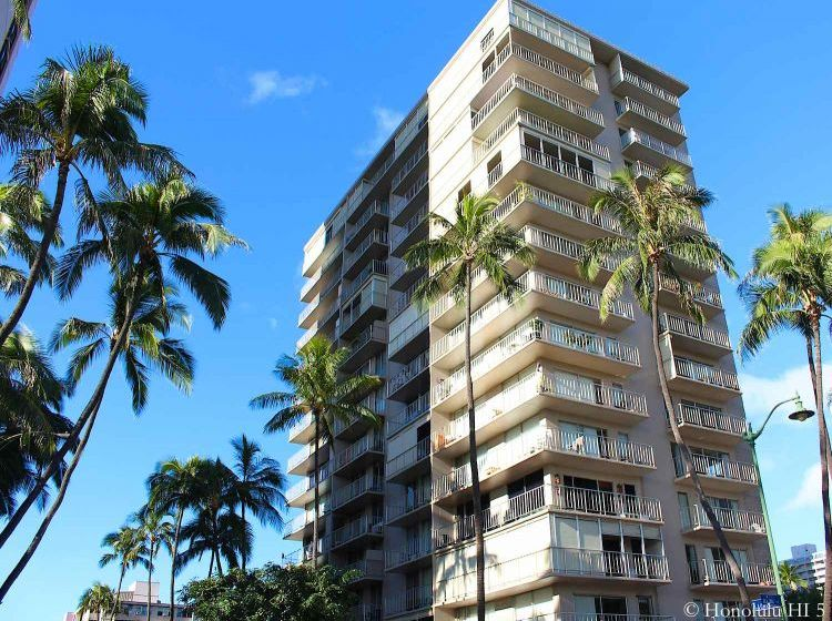 Hale Moani Condo in Waikiki Seen From an Angle. Narrow Deep Building. Looks Older But Well-kept White High-rise