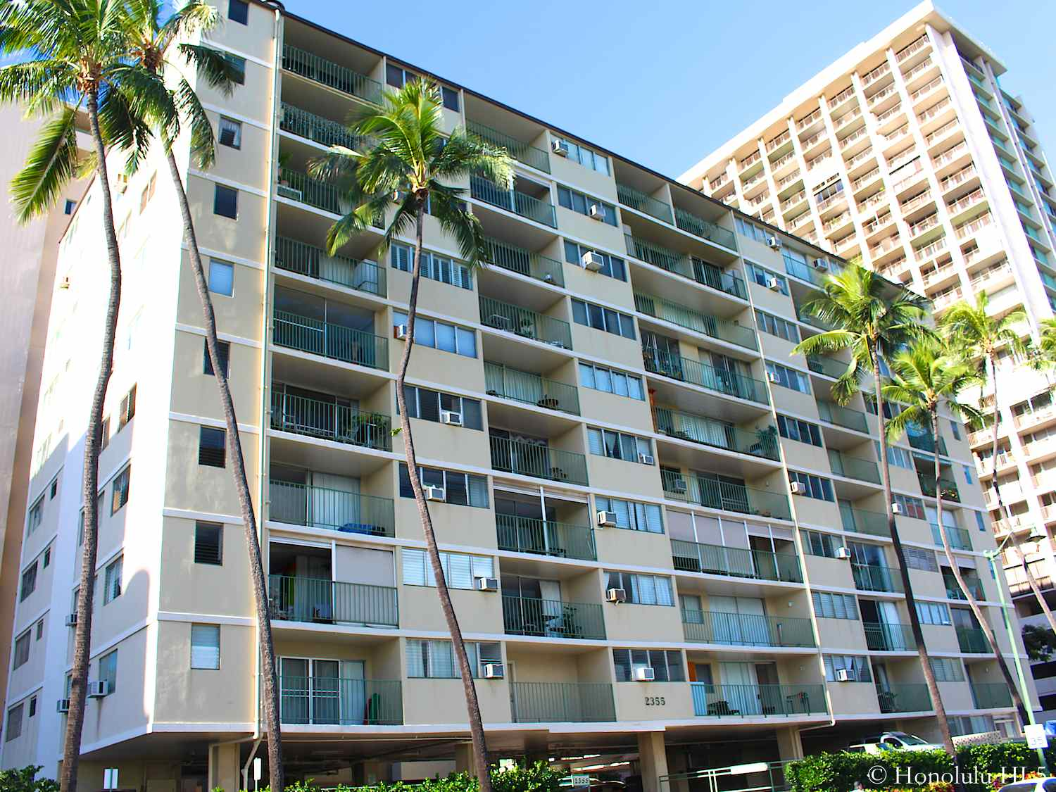 Ala Wai Palms Condos in Waikiki. 10 Story Wide Older Building with Balconies. Off White Color.