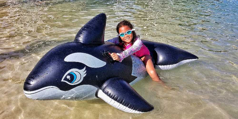 Young Girl With Inflatable Whale in Water